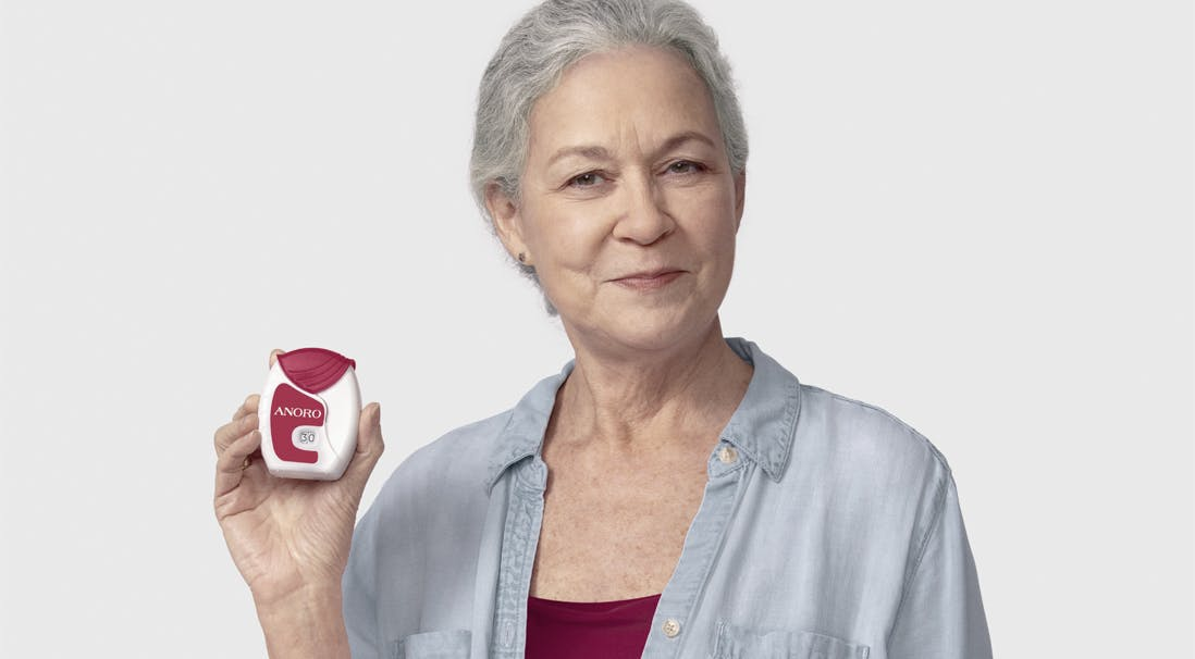 Woman holding ANORO ELLIPTA Inhaler and smiling