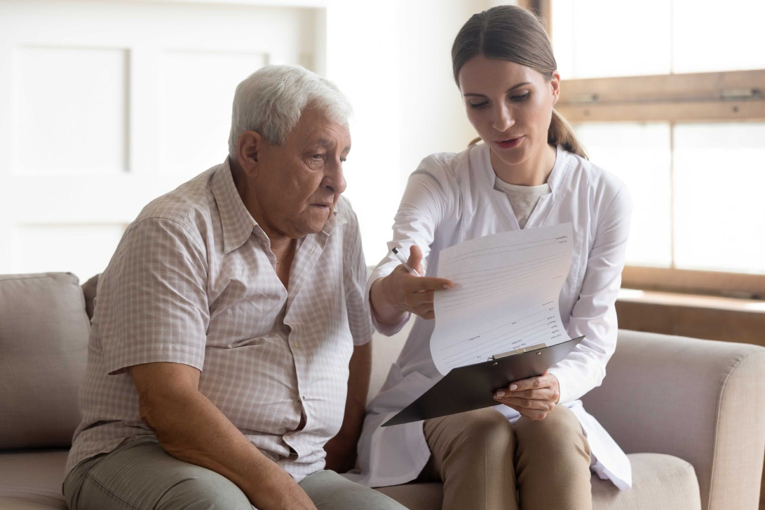 Female medical worker giving consultation to elderly patient