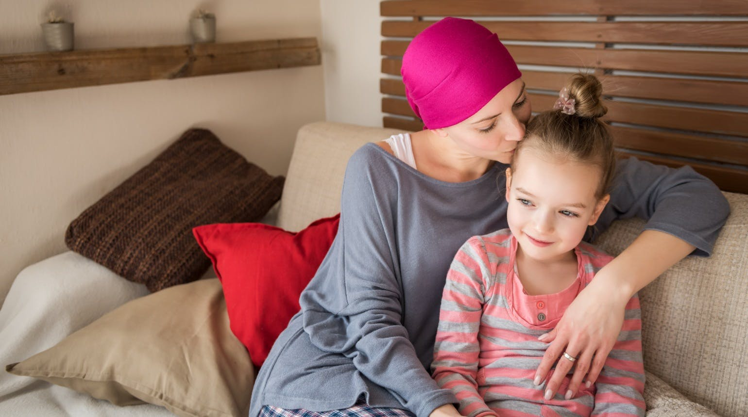 Young adult female cancer patient spending time with her daughter at home, relaxing on the couch