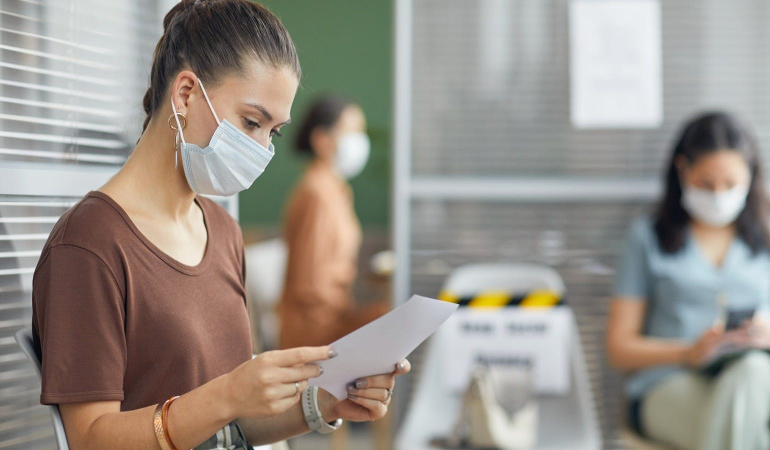 young woman wearing mask and holding document while waiting in line in office