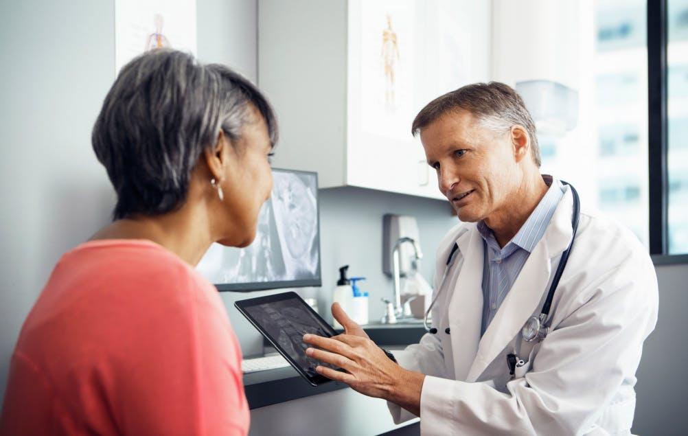 Lupuswissen: Arzt zeigt Patientin Ultraschall auf iPad