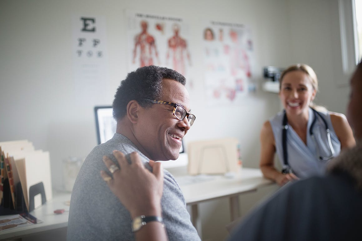 Aging man with HIV interacts with healthcare team in medical clinic.