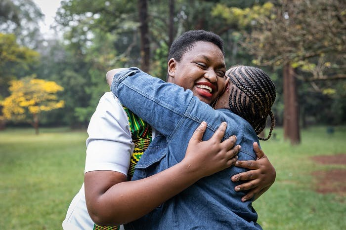 Young woman living with HIV photographed with her friend in Nairobi, Kenya