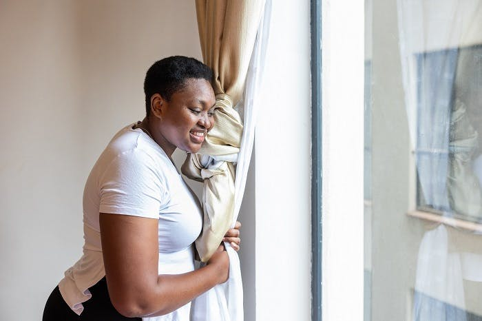 A woman living with HIV looks out of a window and smiles